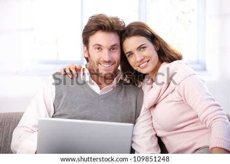 Happy young couple sitting on sofa at home, browxing internet, smiling at camera.