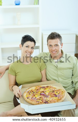 Happy young couple sitting on sofa at home eating pizza, smiling.