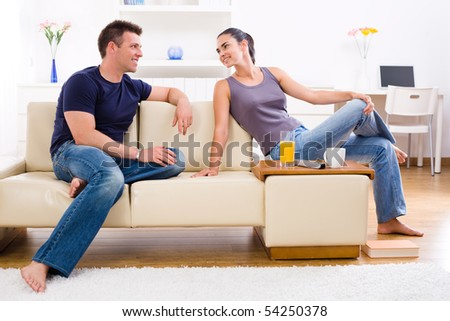 Happy young couple sitting on sofa at home, smiling.