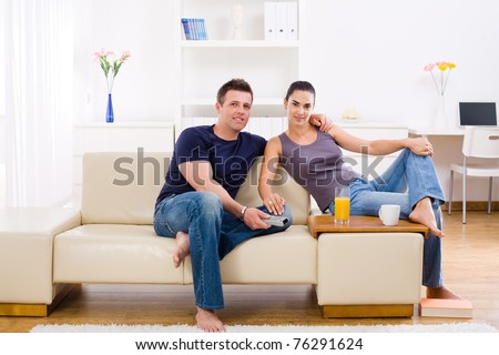 Happy young couple sitting on sofa at home, smiling.?