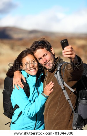 Happy young couple smiling hiking outdoors on travel taking self portrait picture with camera or mobile phone. Asian Caucasian couple on holidays. Photo from volcano Teide, Tenerife, Canary Islands