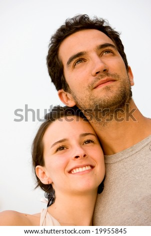 happy young couple smiling outdoors looking away