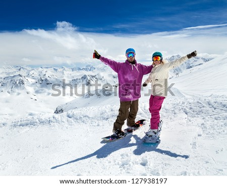 Happy young couple snowboarders in mountains of Alps