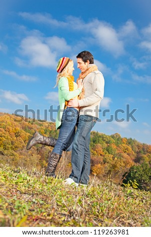Happy young couple spending time outdoor in autumn park