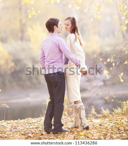happy young couple spending time outdoor in the autumn park
