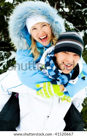 happy young couple spending time outdoor in winter park