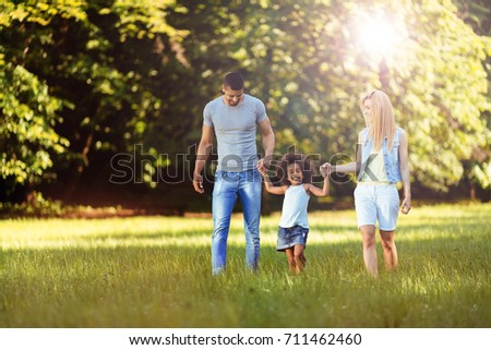 Happy young couple spending time with their daughter - Shutterstock ID 711462460