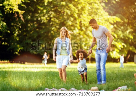 Happy young couple spending time with their daughter - Shutterstock ID 713709277