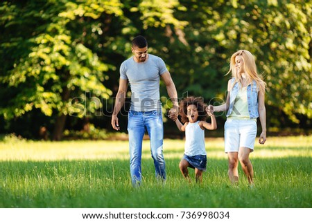 Happy young couple spending time with their daughter - Shutterstock ID 736998034
