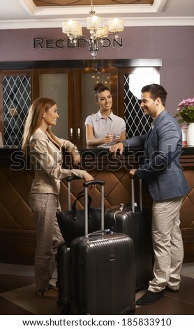 Happy young couple standing at hotel reception, checking in upon arrival, smiling.