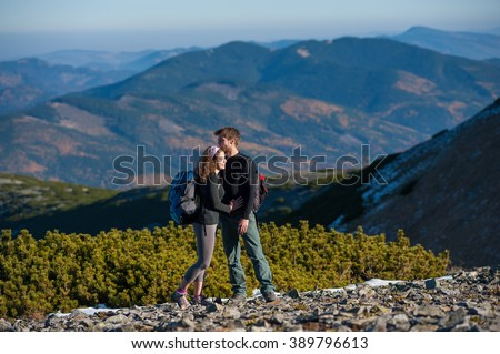 Happy young couple standing enjoying a break during hike on vacation, smiling and hugging each other. Big beautiful mountains on the background. Warm and sunny autumn day. - Shutterstock ID 389796613