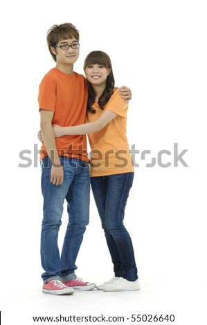 Happy young couple standing together against white background