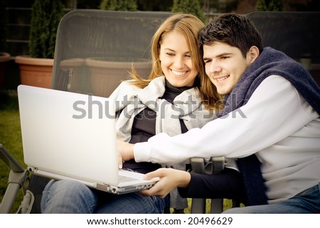 Happy Young couple surfing the internet outside - stock photo