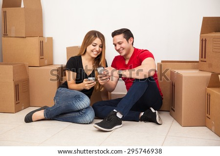 Happy young couple taking a break from unpacking and sharing photos with their smartphones