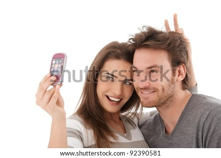 Happy young couple taking a photo of themselves, smiling.?