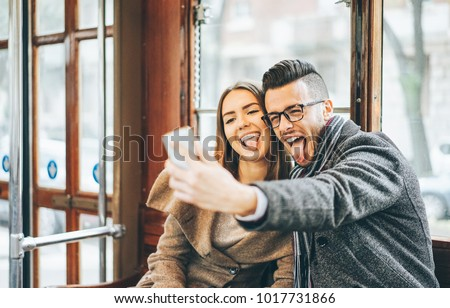 Happy young couple taking photos using mobile smart phone camera inside bus - Travel lovers making a self portrait to post on social media network - Relationship, love, smartphone addiction concept
