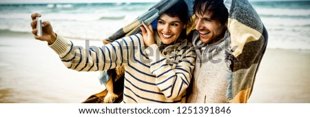 Happy young couple taking selfie at beach during winter