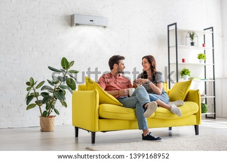 happy young couple talking and holding cups while sitting on yellow sofa under air conditioner at home Foto stock ©