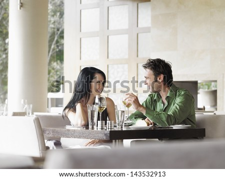 Happy young couple talking over wine at outdoor restaurant