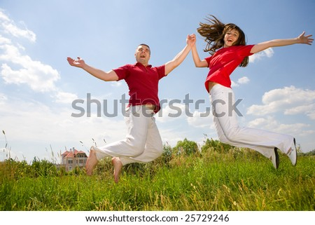 Happy Young Couple - team is jumping