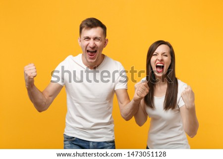 Happy young couple two friends guy girl in white empty blank design t-shirts posing isolated on yellow orange background. People lifestyle concept. Mock up copy space. Doing winner gesture, screaming #1473051128
