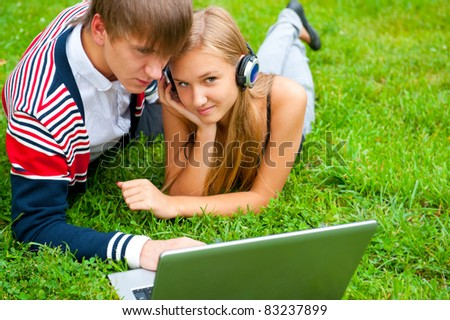 Happy young couple using laptop while lying on grass