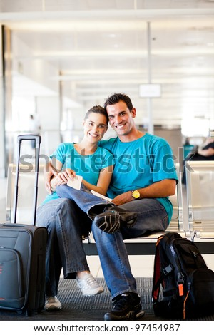 happy young couple waiting for flight at airport - stock photo