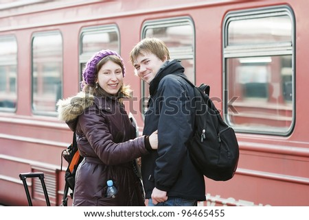Happy young couple waiting for train on railway station platform