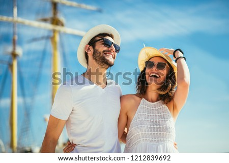 Happy young couple walking by the harbor of a touristic sea resort with sailboats on background #1212839692