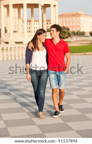 Happy Young Couple Walking Embraced