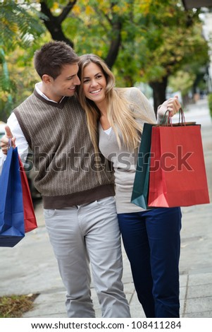 Happy young couple walking leisurely together on sidewalk with shopping bags