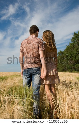 Happy young couple walking on a field - outdoors.