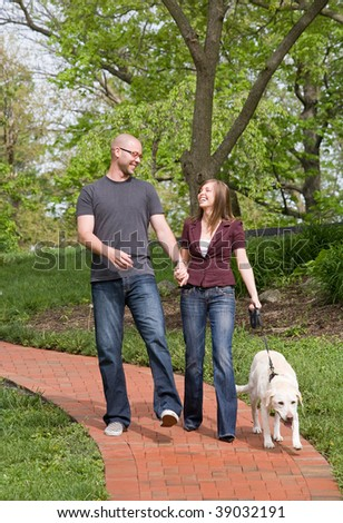 Happy Young Couple Walking Their Dog