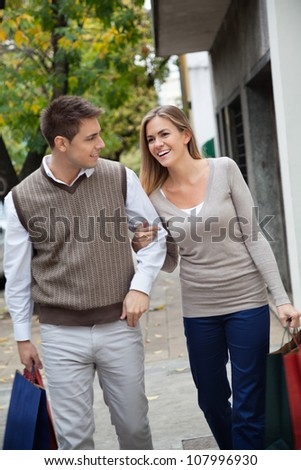 Happy young couple walking together on pavement with shopping bags