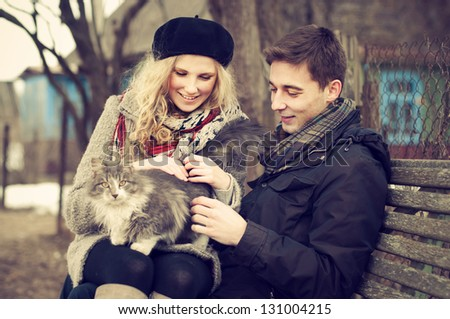 happy young couple with a cat on a bench near the house