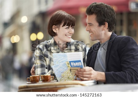 Happy young couple with a guidebook at an outdoor cafe