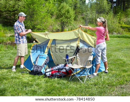 Happy young couple with big tent. Camping. - stock photo