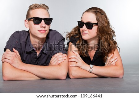 Happy young couple with black sunglasses casual dressed. Studio shot isolated on grey background. Man with short blond hair. Woman long brown hair.