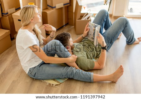 happy young couple with book sitting on floor while moving into new home