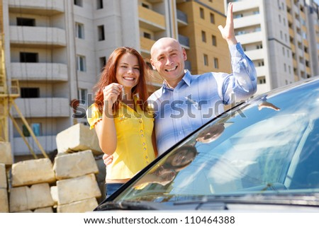 happy young couple with keys against multistory home