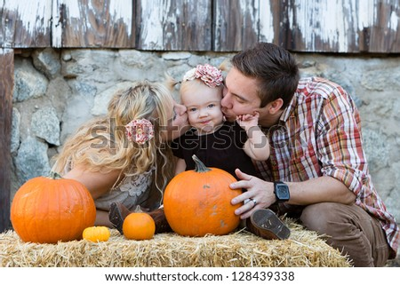 happy young couple with pumpkins; kissing their child