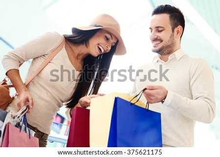 Happy young couple with shopping bags.Image taken inside a shopping mall.