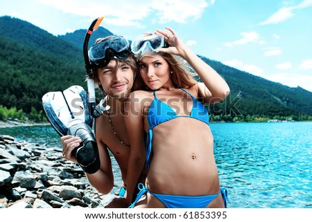Happy young couple with snorkelling gear standing on a sea beach.