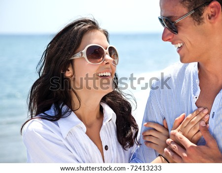 Happy young couple with sunglasses holding hands and hugging on beach