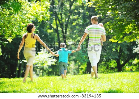 happy young couple with their children have fun at beautiful park outdoor in nature - Shutterstock ID 83194135