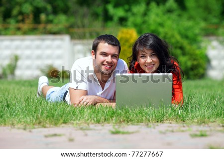 Happy young couple working on their laptop in the park