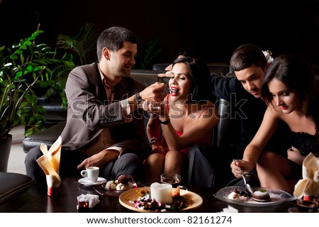 happy young couples eating deserts coffee