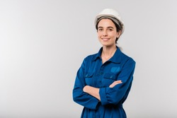 Happy young cross-armed female engineer in blue workwear and hardhat standing in isolation