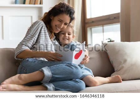 Happy young curly mother relaxing on sofa, embracing small preschool daughter, reading congratulations wishes in birthday card, feeling proud. Excited mommy enjoying greetings in postcard with child.