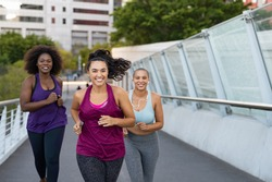 Happy young curvy women jogging together on city bridge. Healthy girls friends running on the city street to lose weight. Group of multiethnic oversize women running with building in the background.